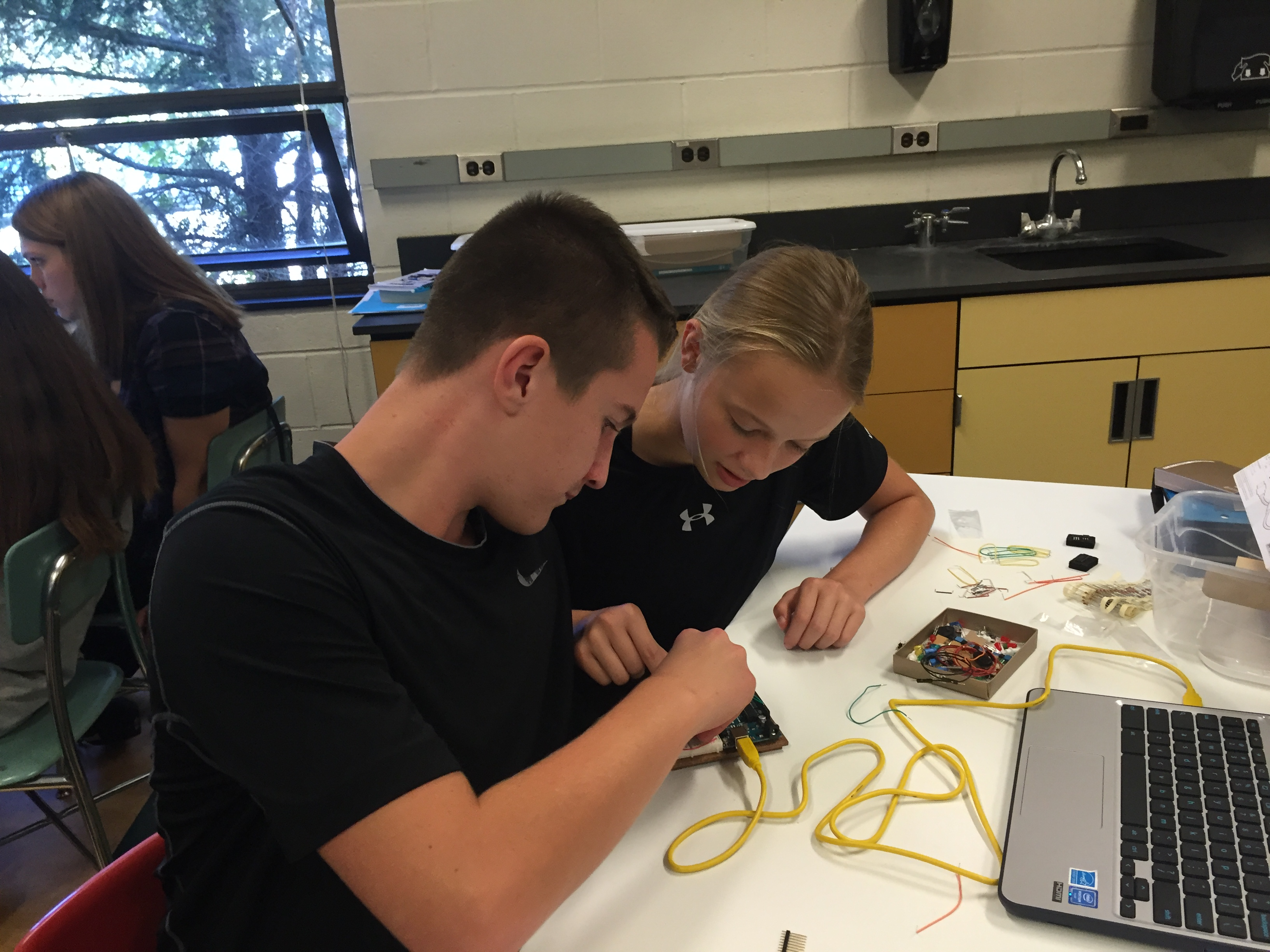 Two students working on an arduino device.