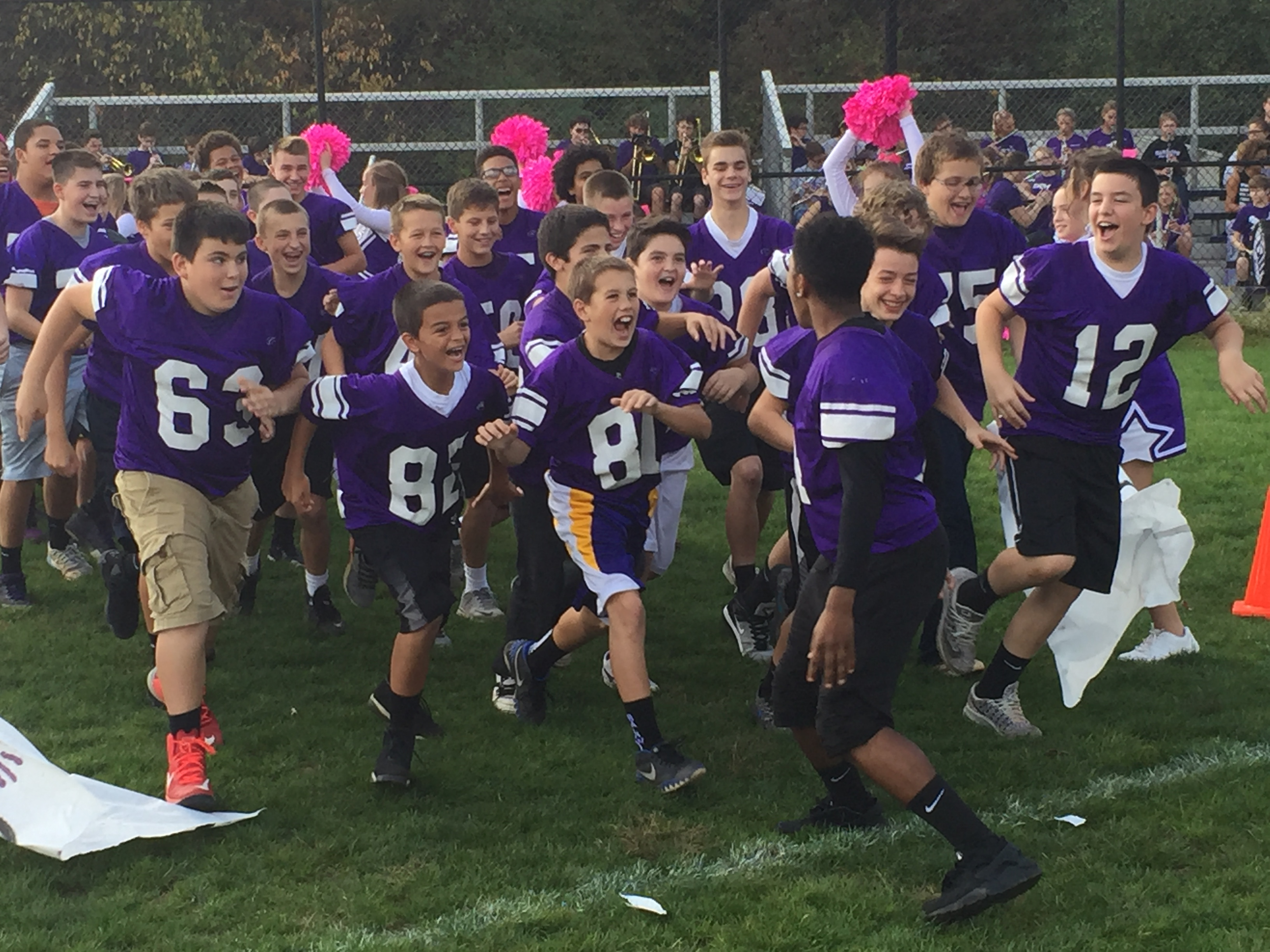 Football team running through a banner on a pep rally day.